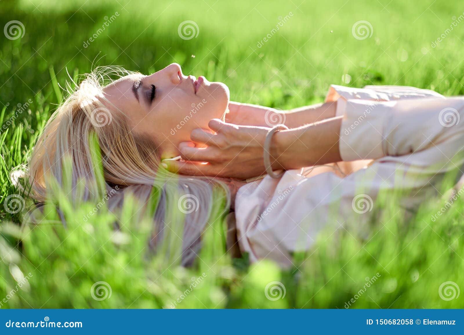 La femme a clôturé ses yeux et musique de écoute avec ses écouteurs et se situer dans le pré Appr?cie la musique, d?tend