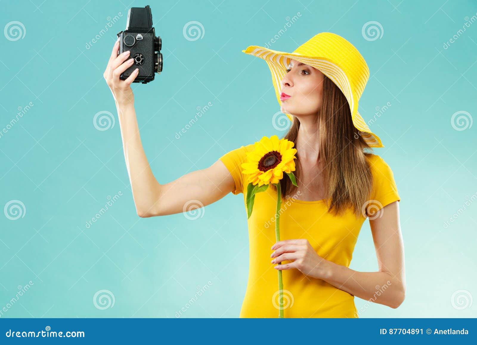 La femme d été tient le vieil appareil-photo de tournesol