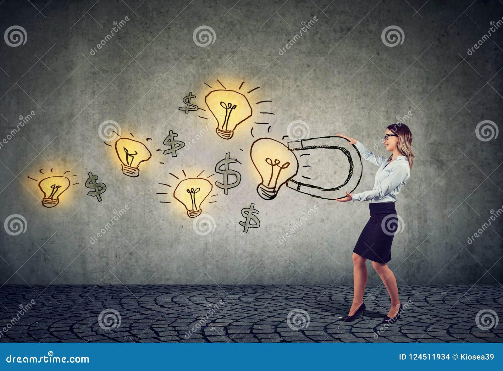 La femme d affaires attire les ampoules d idées lumineuses avec un grand aimant