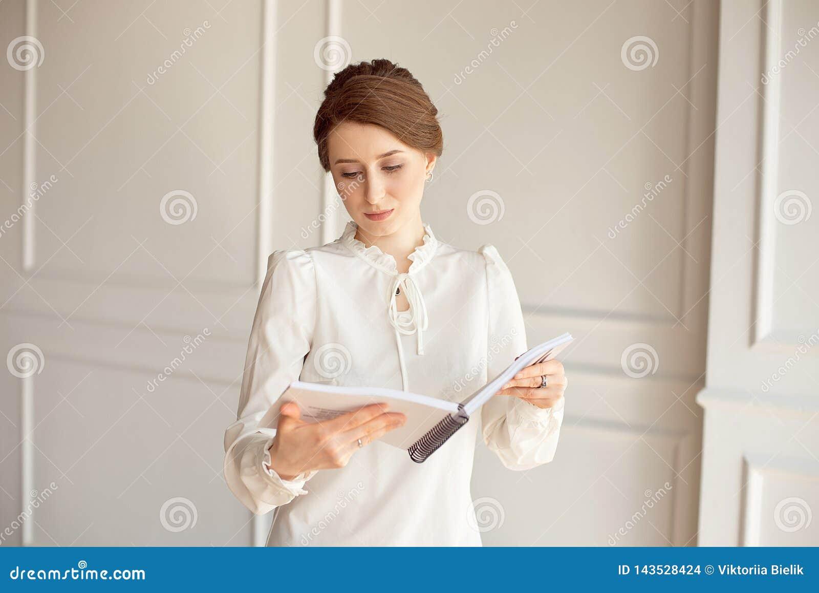 La femme d affaires dans une chemise blanche et des pantalons noirs regarde des documents dans des mains