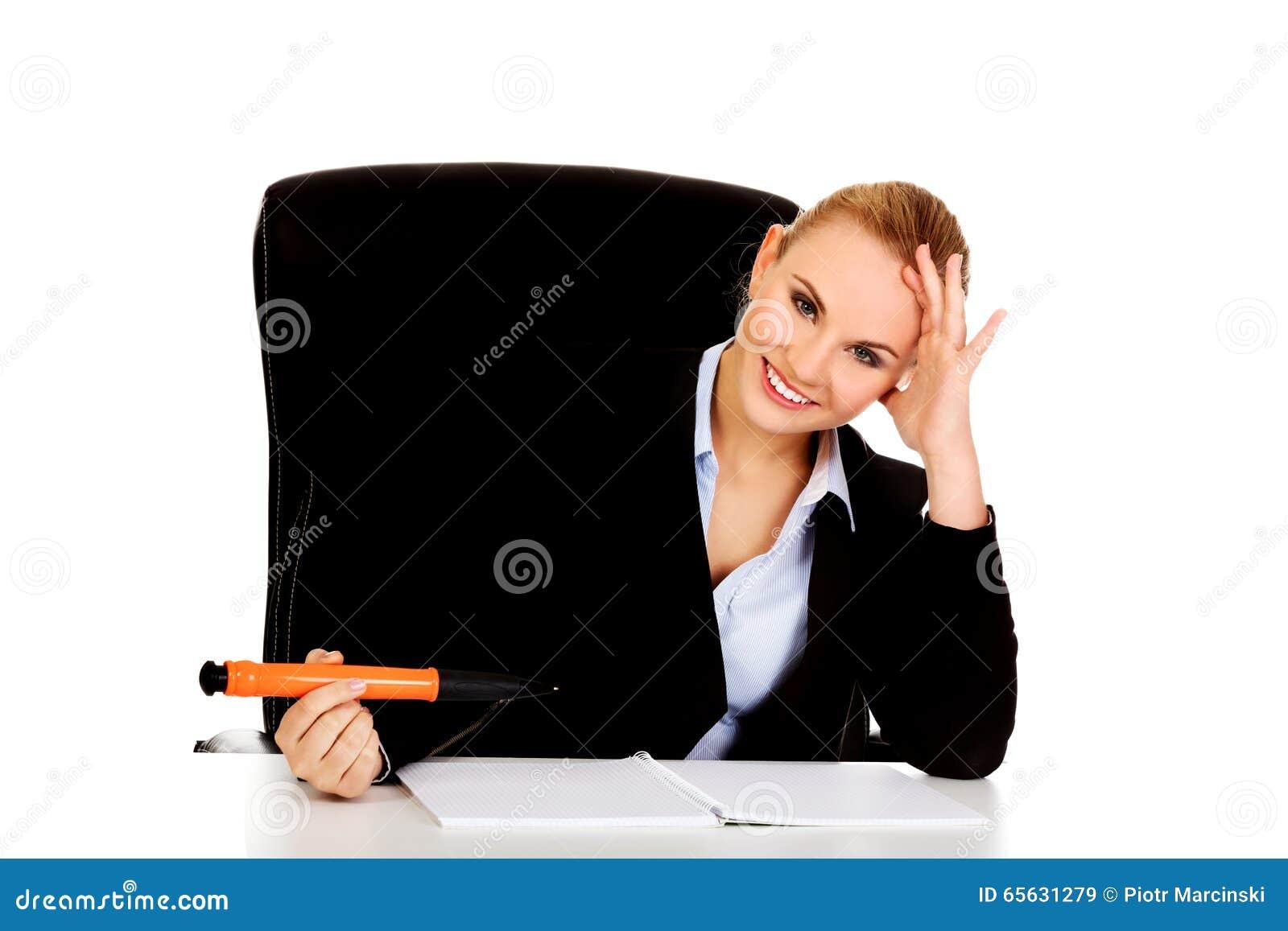 La femme d affaires s asseyant derrière le bureau et écrit quelque chose avec le grand stylo