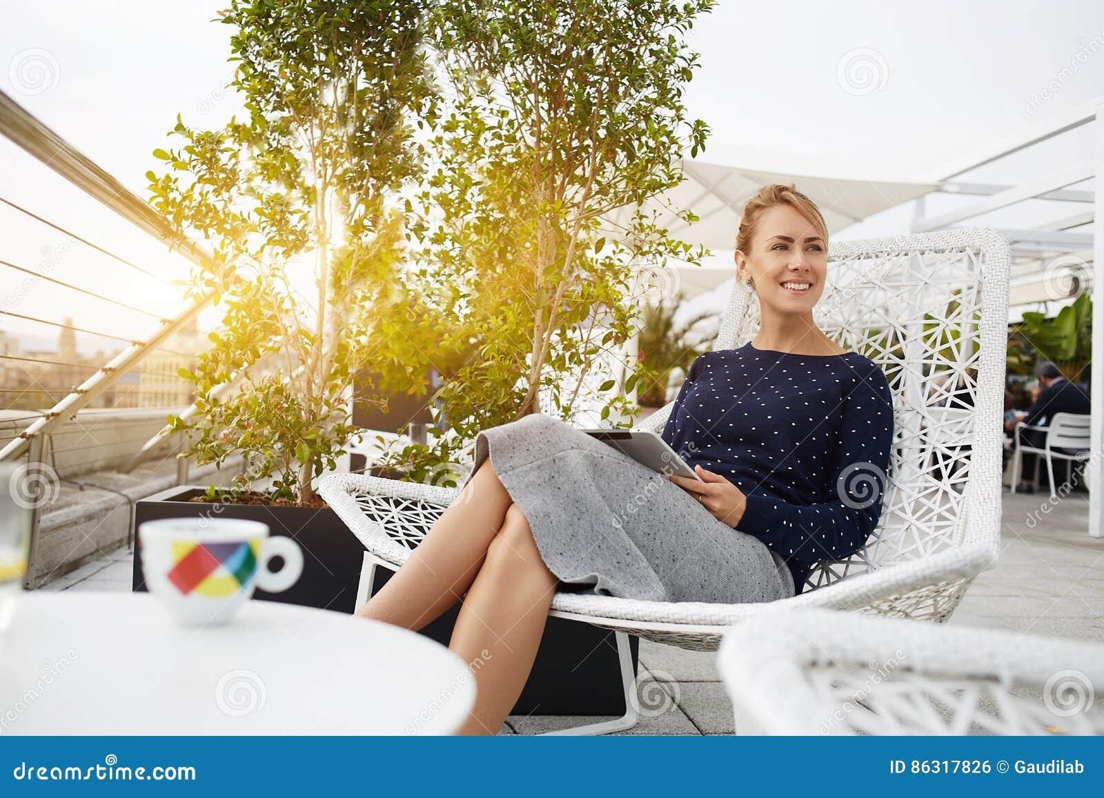 La femme d affaires sourit pour quelqu un, tandis que se repose avec le pavé tactile portatif dans le restaurant à l air frais