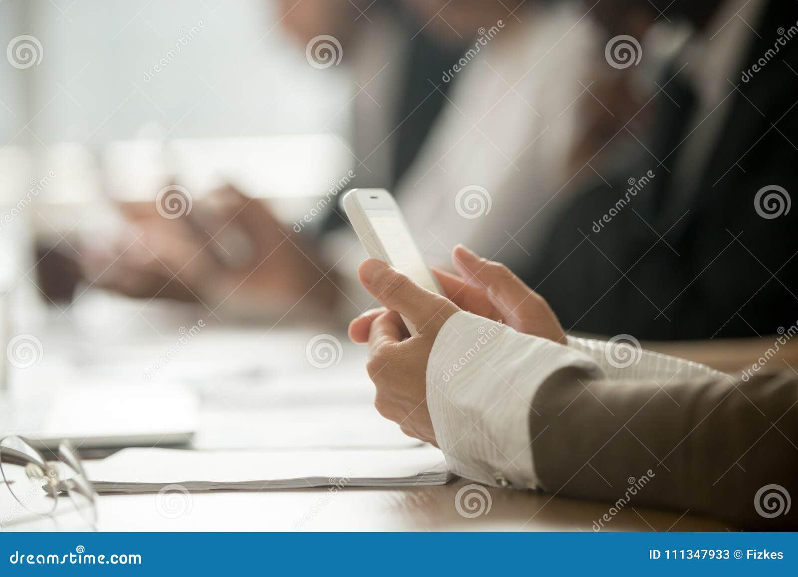 La femme daffaires tenant le téléphone portable lors de la réunion