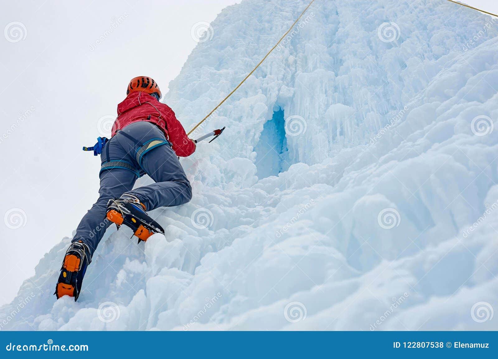 La femme d alpiniste avec de la glace usine la hache dans le casque orange montant un l