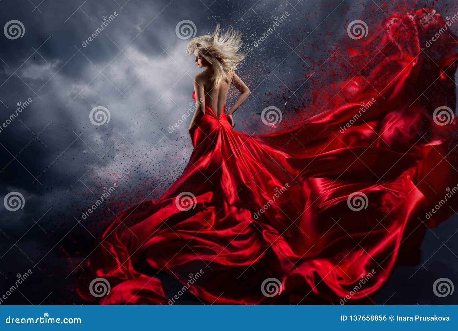 La femme dans la danse rouge de robe au-dessus du ciel de tempête, habillent le tissu de flottement