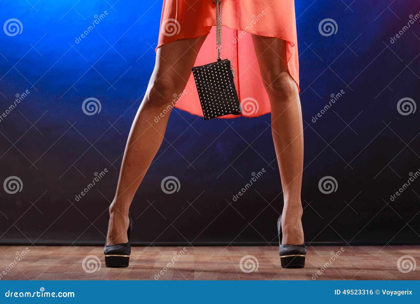 La femme dans des talons tient le sac à main, club de disco