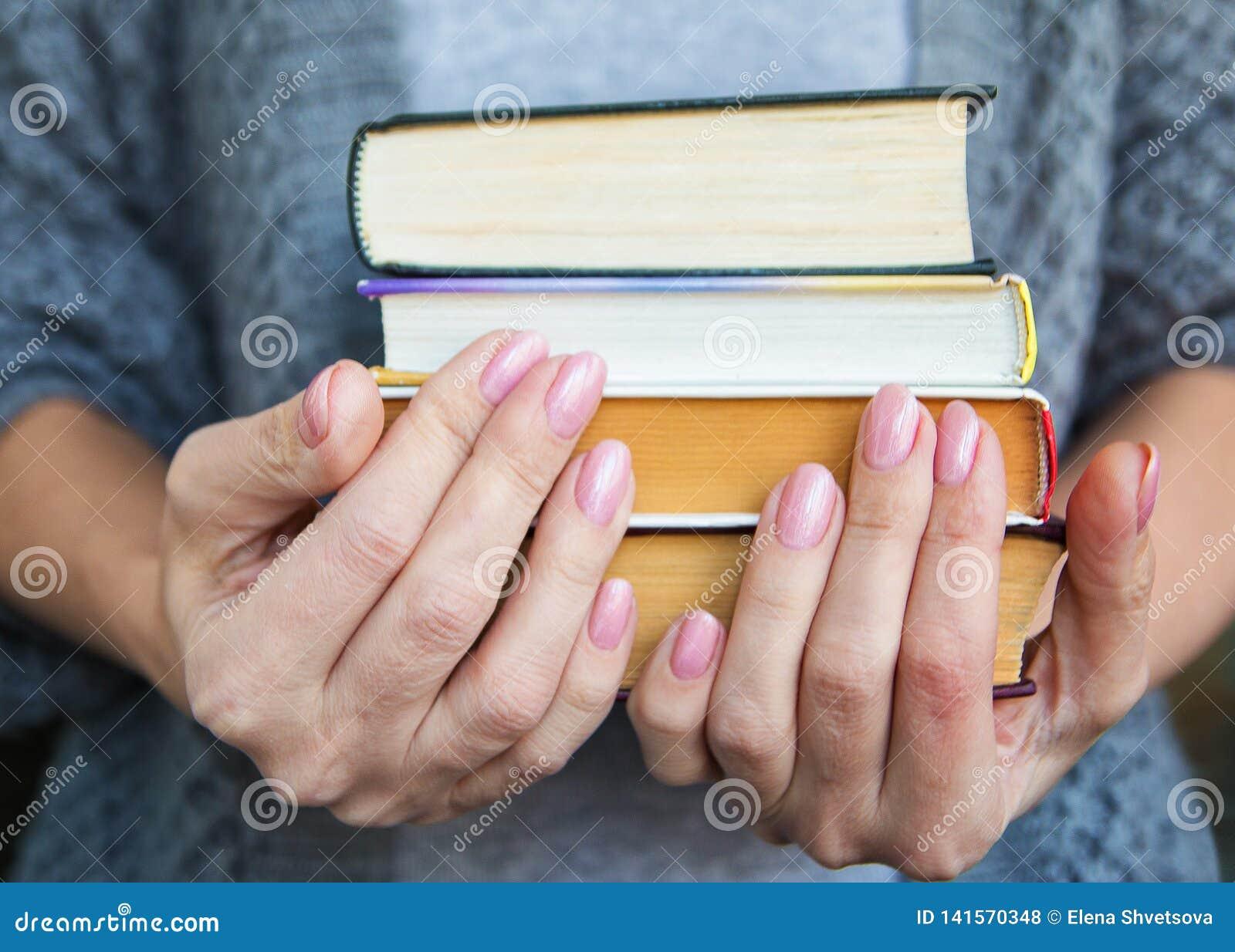 La femme dans des vêtements gris tient quatre livres à disposition
