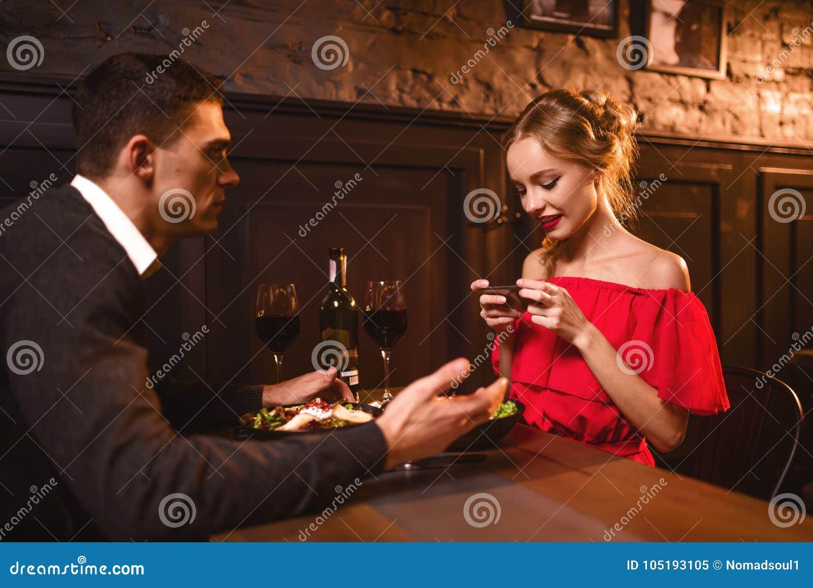 La femme dans la robe rouge fait l image de son homme au téléphone