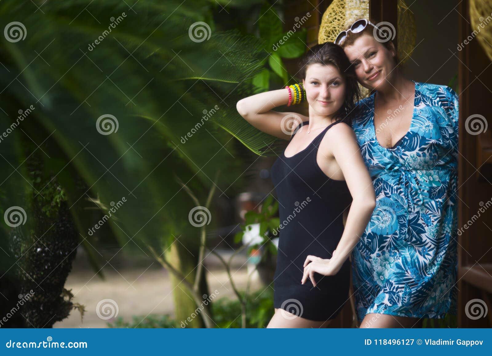 La femme dans une robe bleue ainsi qu une jeune belle femme dans une robe noire se tient à la porte de elle hous