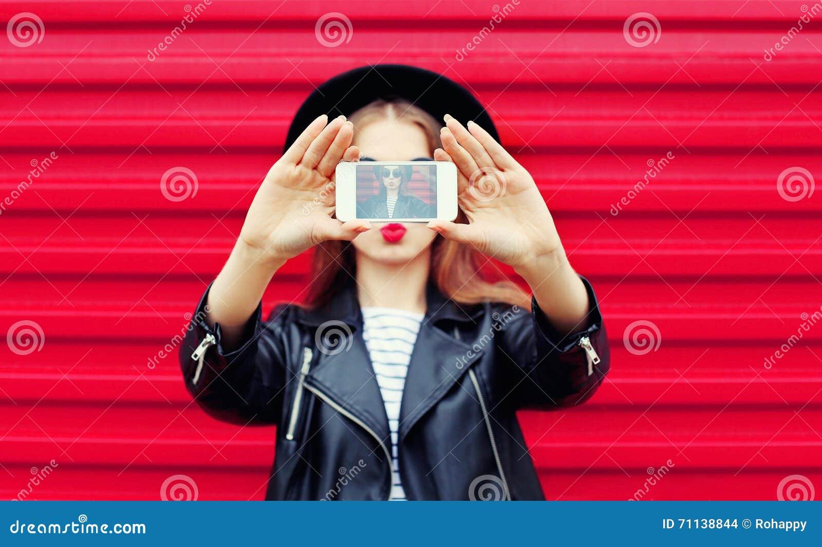 La femme de charme de mode fait l autoportrait sur les lèvres de soufflement de smartphone au-dessus du rose de ville