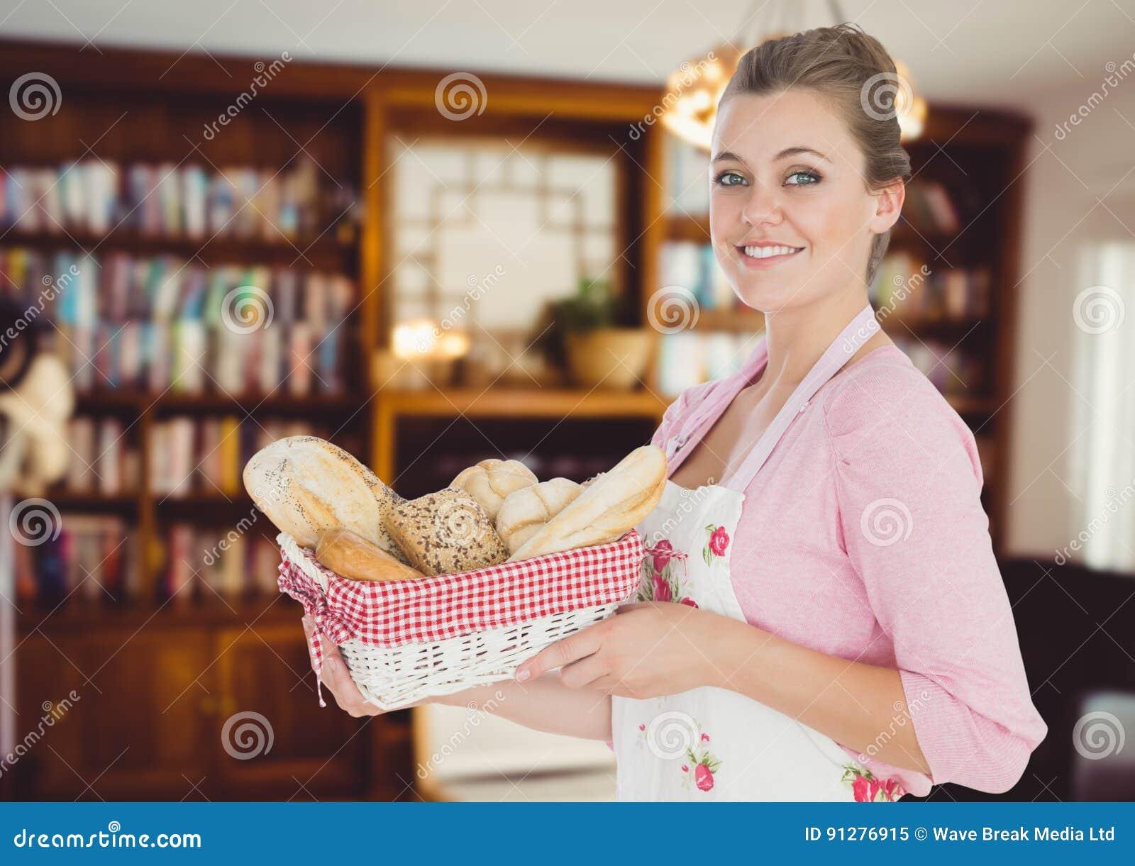 La femme de cuisinier avec du pain se dorent dans le salon