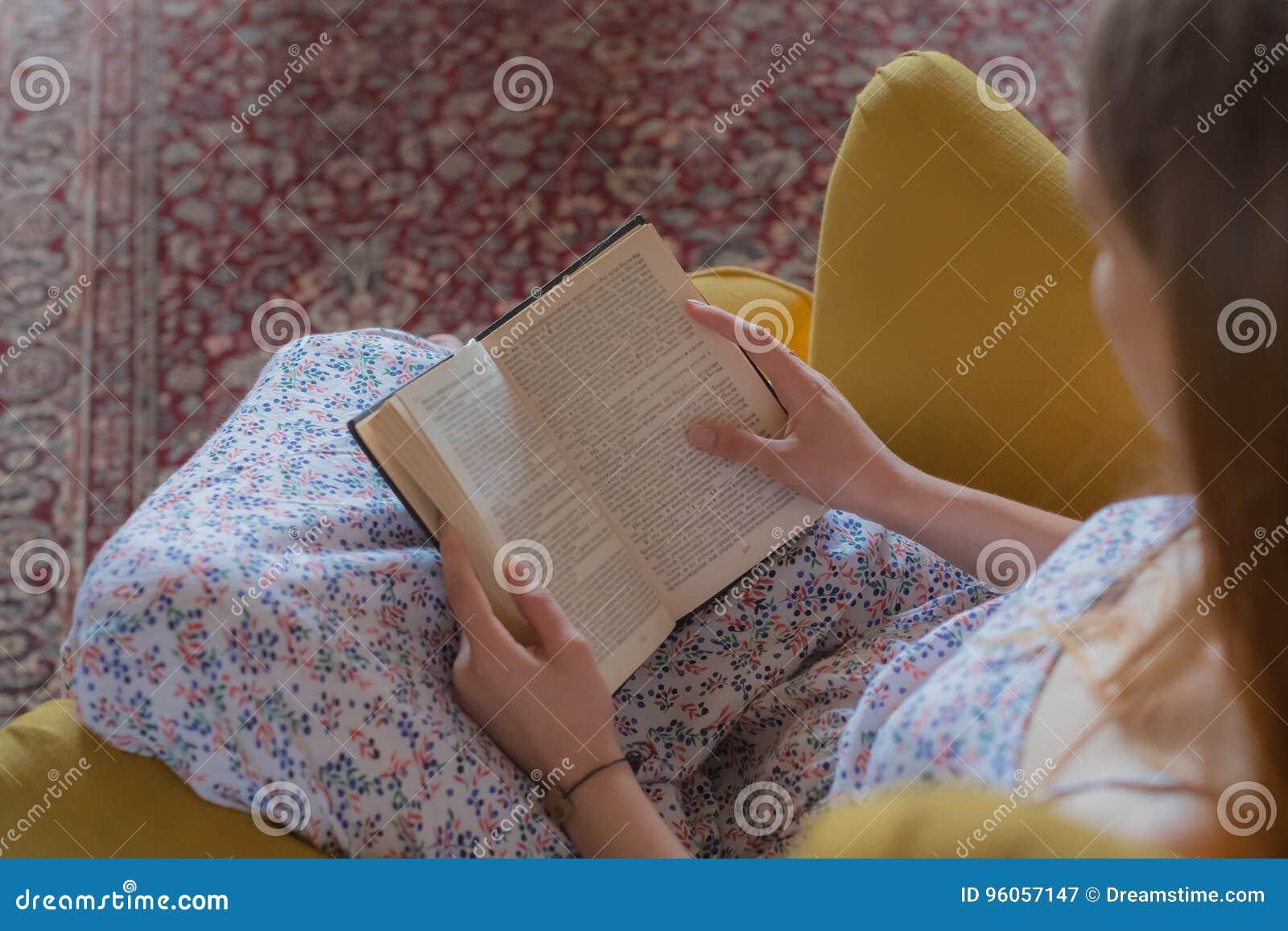 La femme de l adolescence a lu la chaise de livre à l intérieur