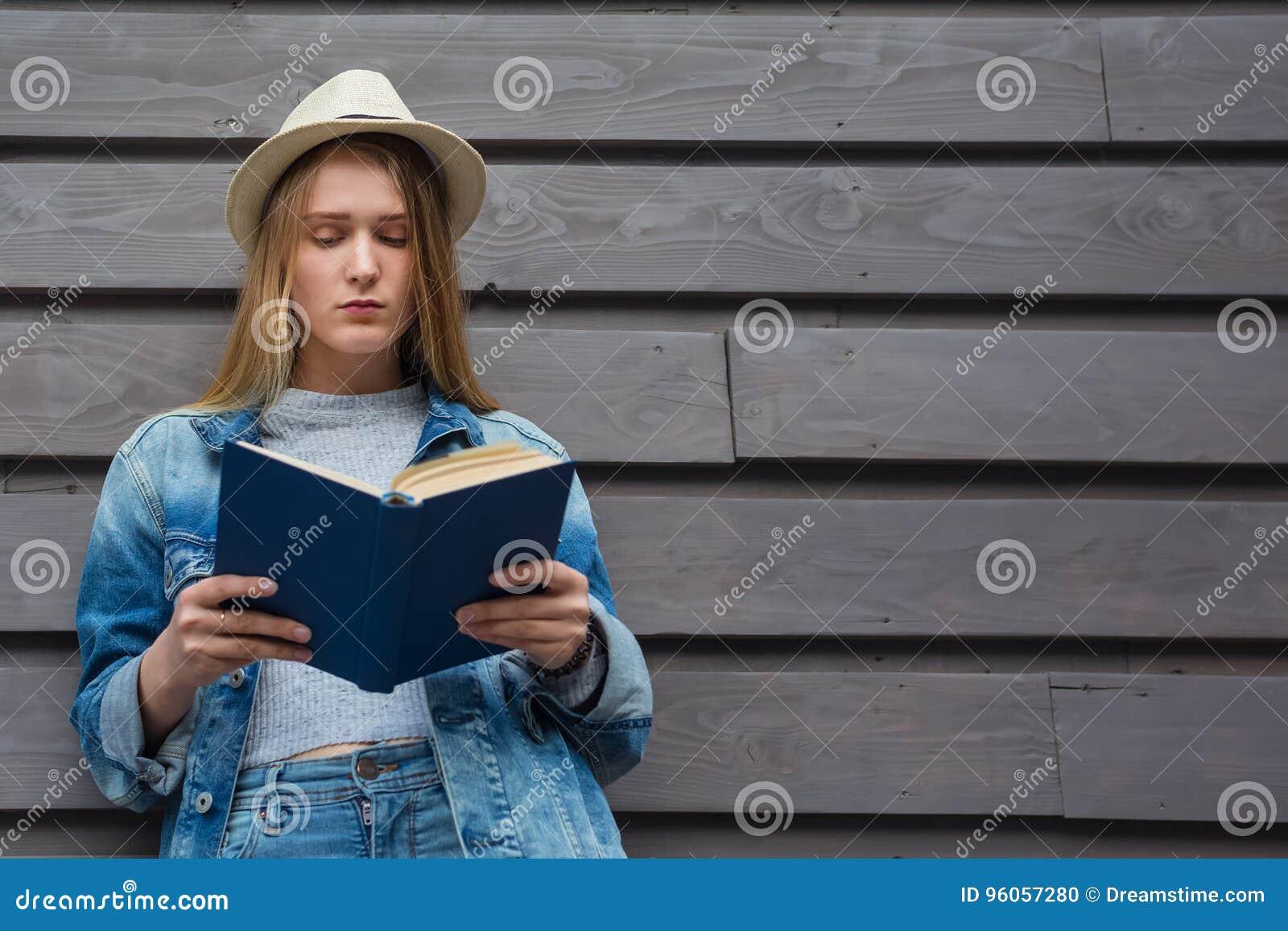 La femme de l adolescence a lu le livre en dehors du mur