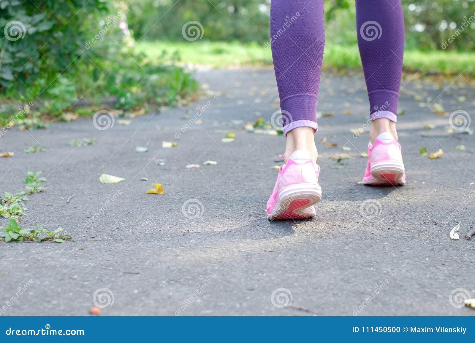 La femme de marche et pulsante avec les jambes sportives et les chaussures de course, se ferment, Copyspace pour votre texte