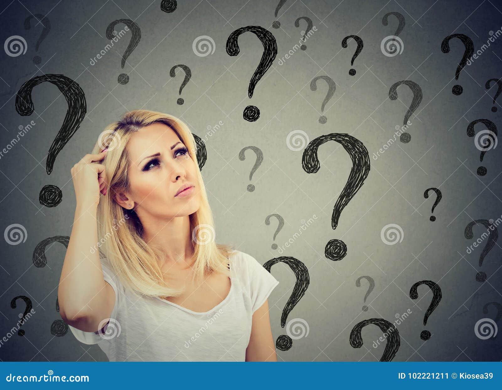 La femme de pensée confuse par portrait déconcertante rayant la tête cherche une solution regardant beaucoup de points d interrog