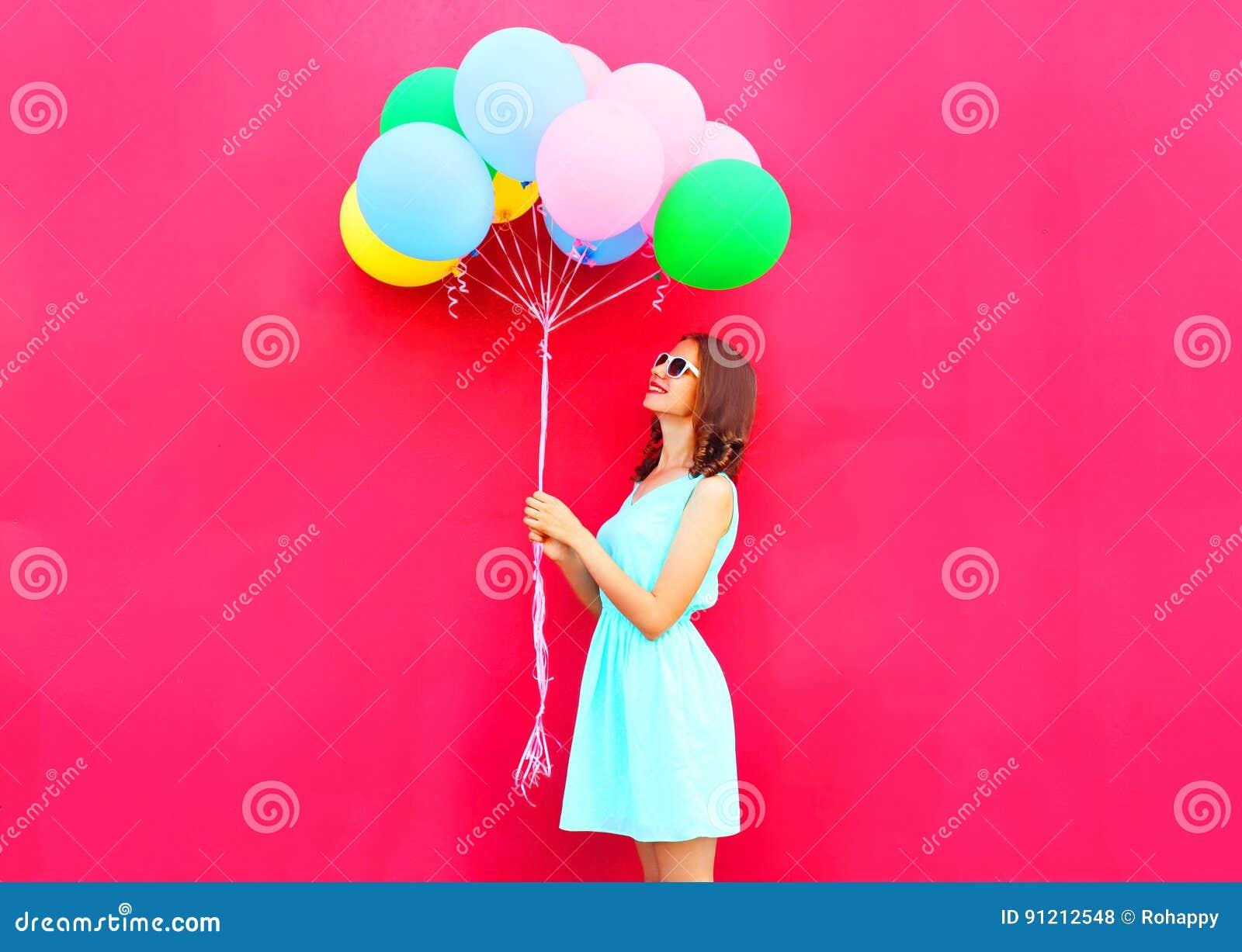 La femme de sourire heureuse regarde sur les ballons colorés d un air ayant l amusement au-dessus du fond rose
