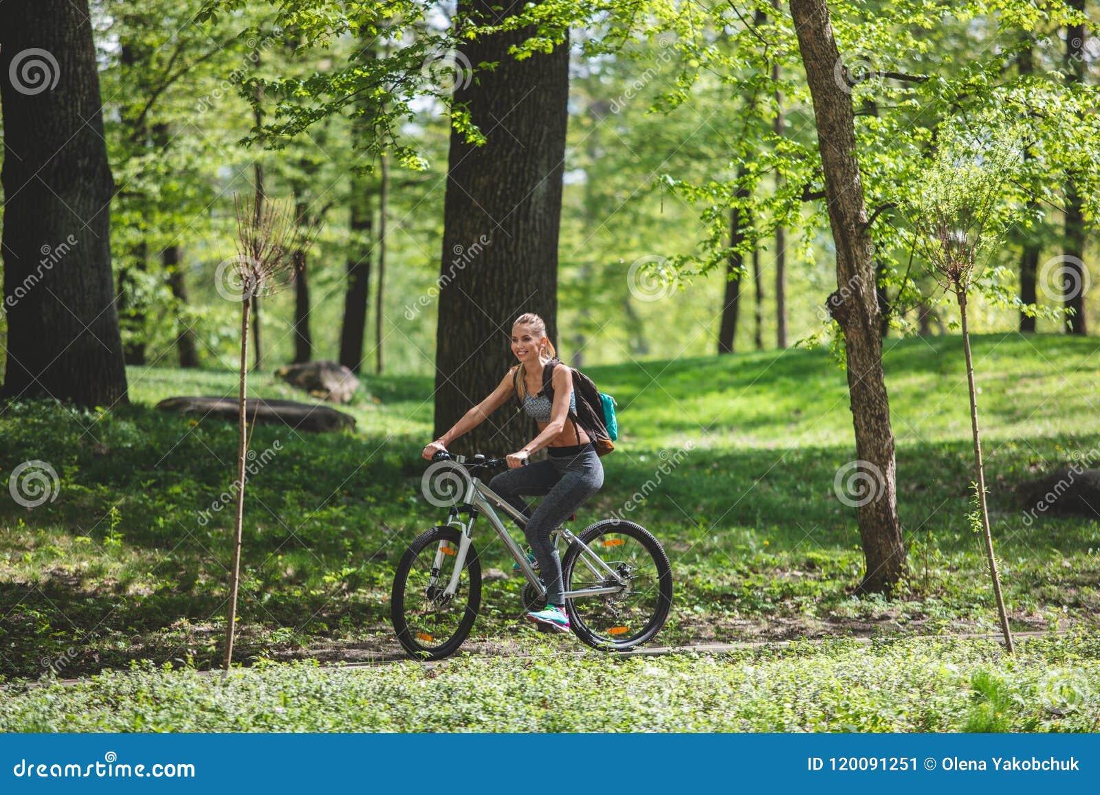 La femme de sourire monte le long du chemin en bois