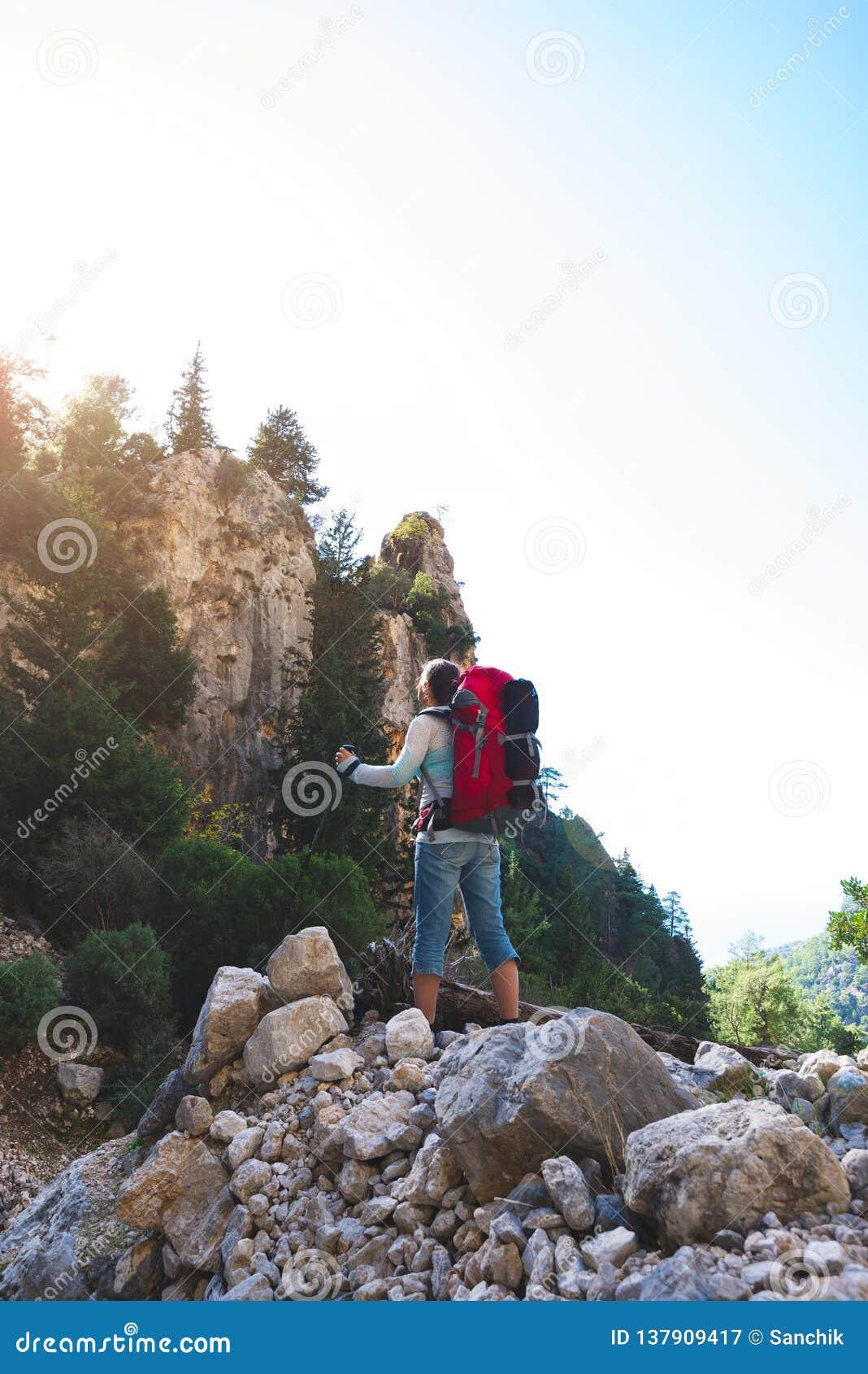 La femme de voyageur se tient sur la pierre