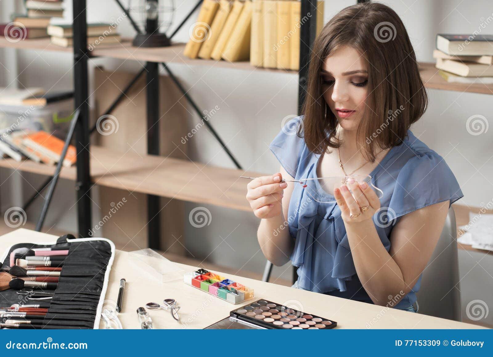 La femme dessine sur la palette en verre avec la peinture théâtrale