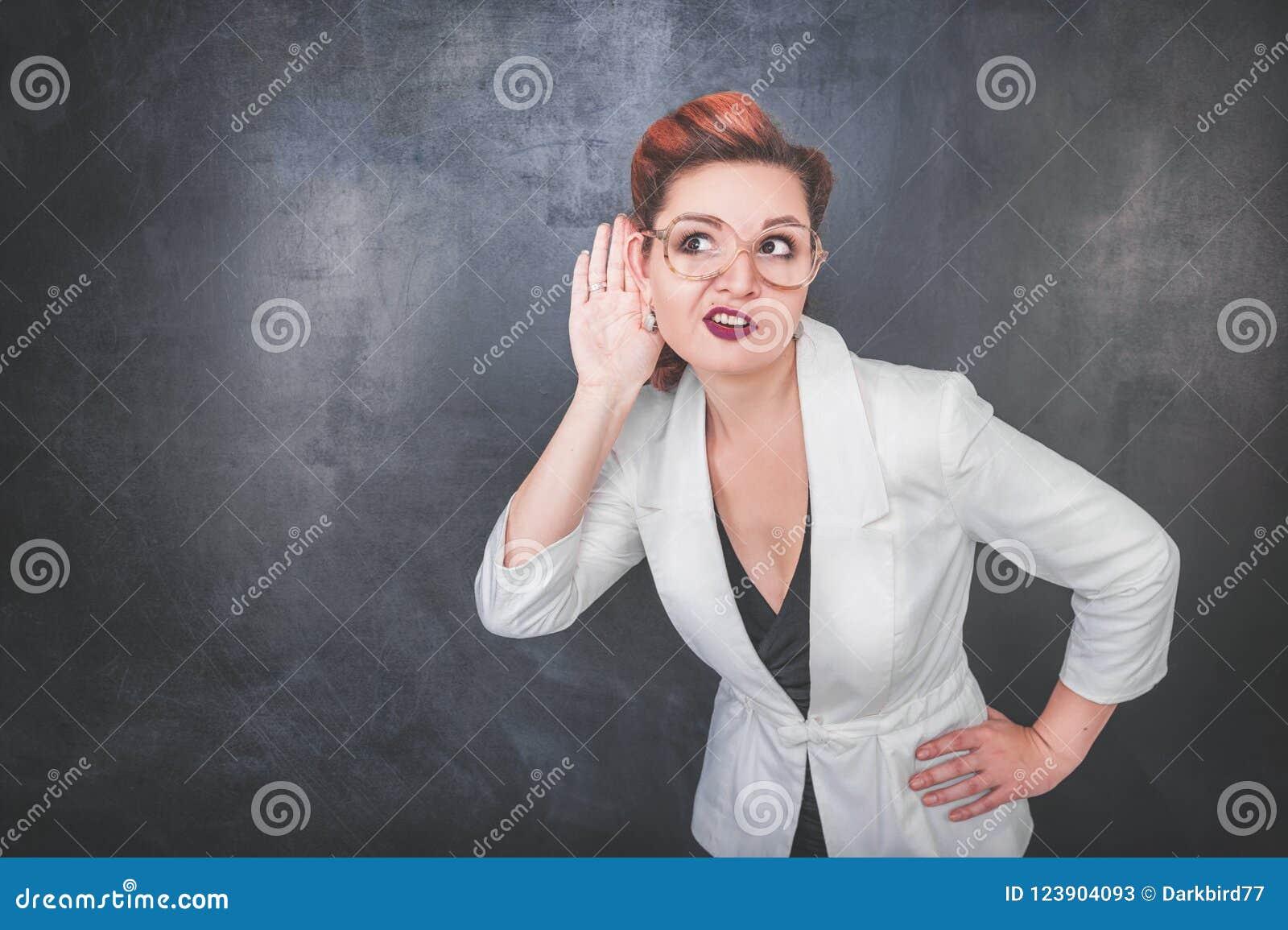 La femme drôle écoutent clandestinement le fond de tableau noir