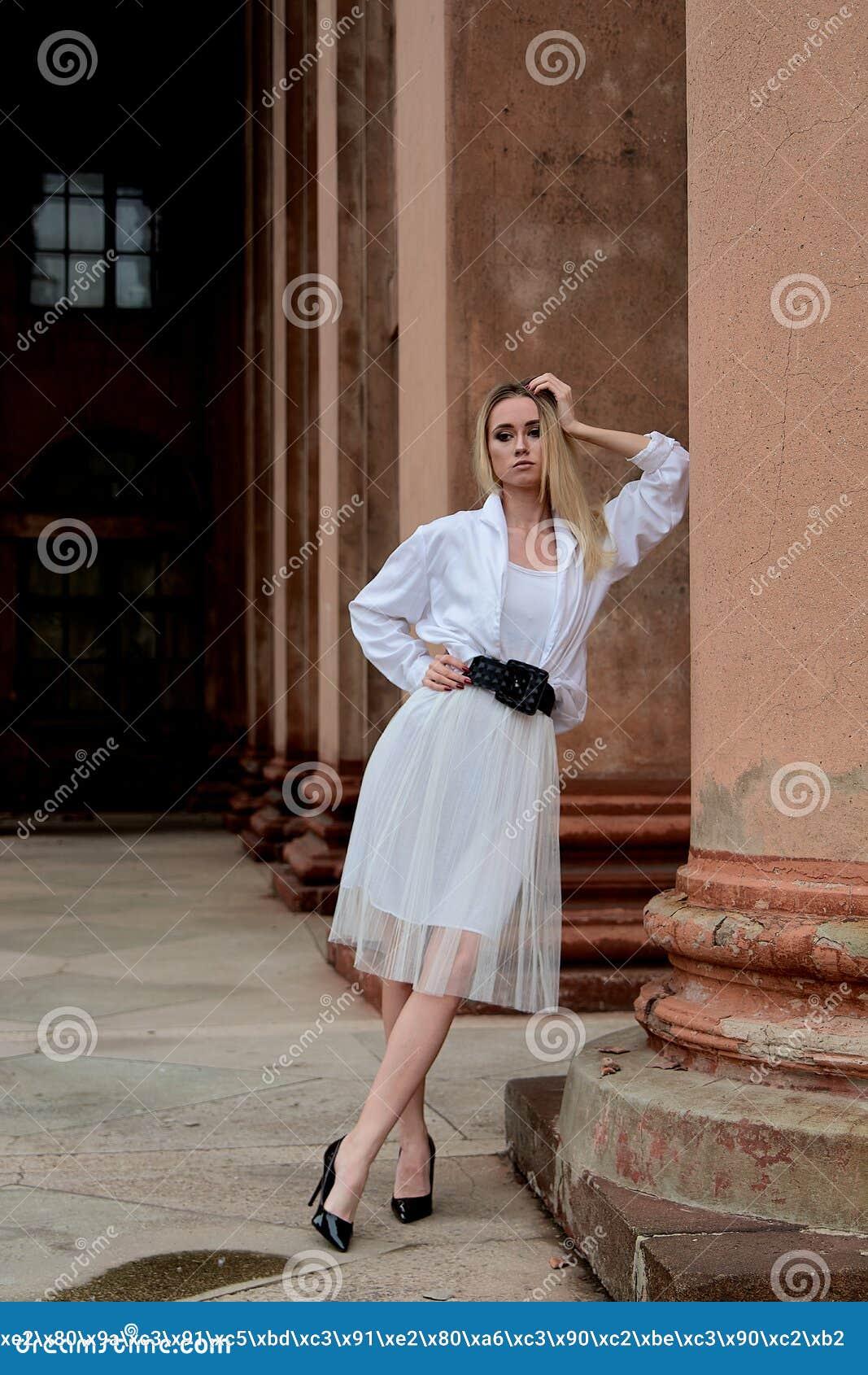 La femme du regard de mode Portrait moderne de jeune femme Jeune femme habillée dans la jupe blanche et la chemise posant près du