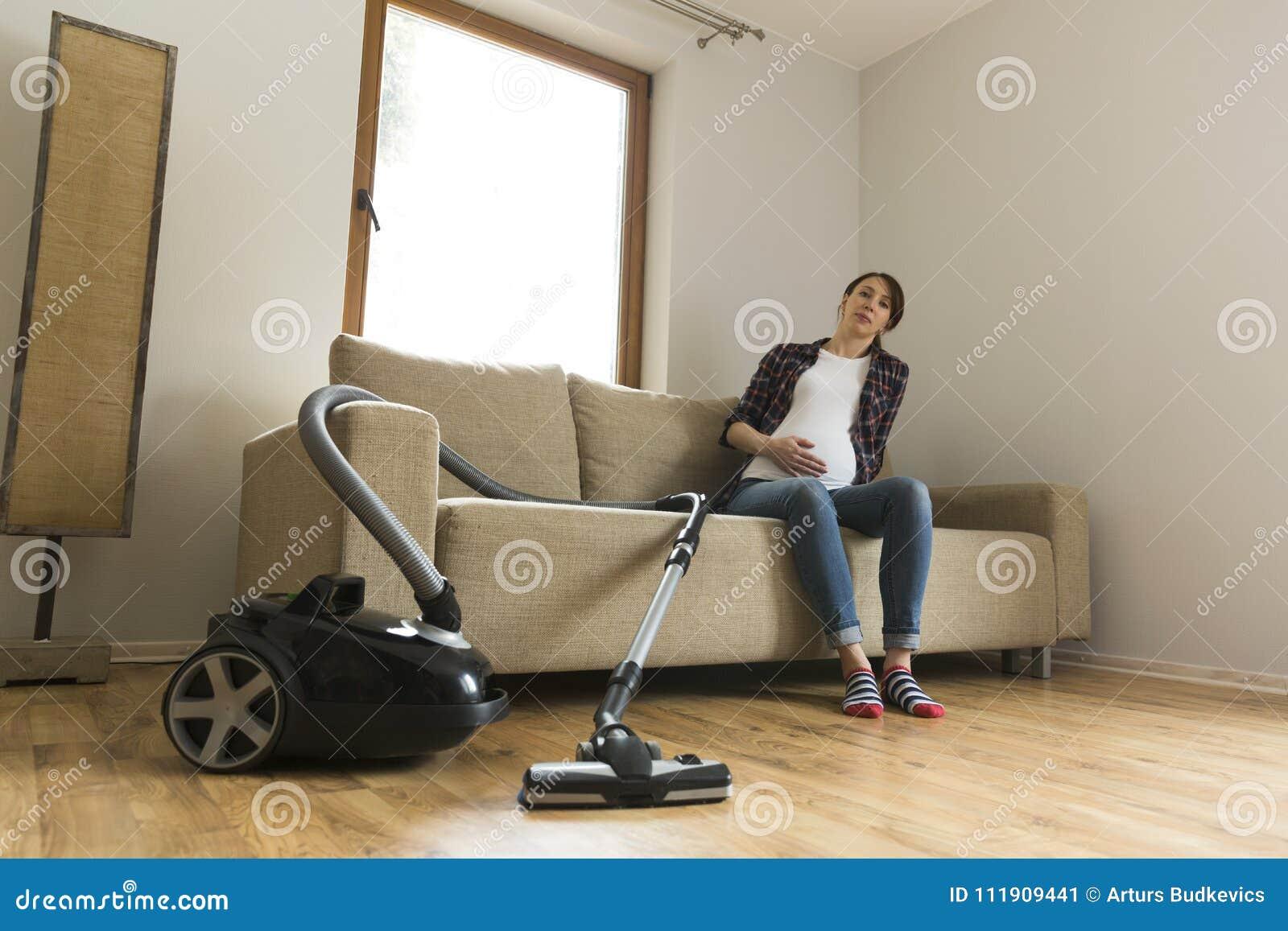 La femme enceinte s asseyant sur le divan a fatigué de nettoyer à l aspirateur Concept de ménage et de grand nettoyage