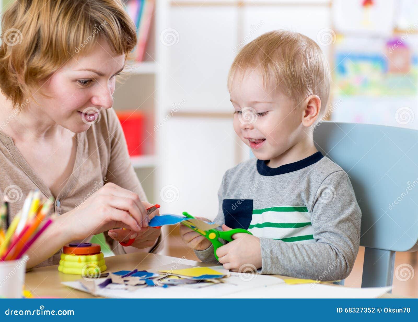 La femme enseigne l enfant handcraft au jardin d enfants ou le playschool ou la maison