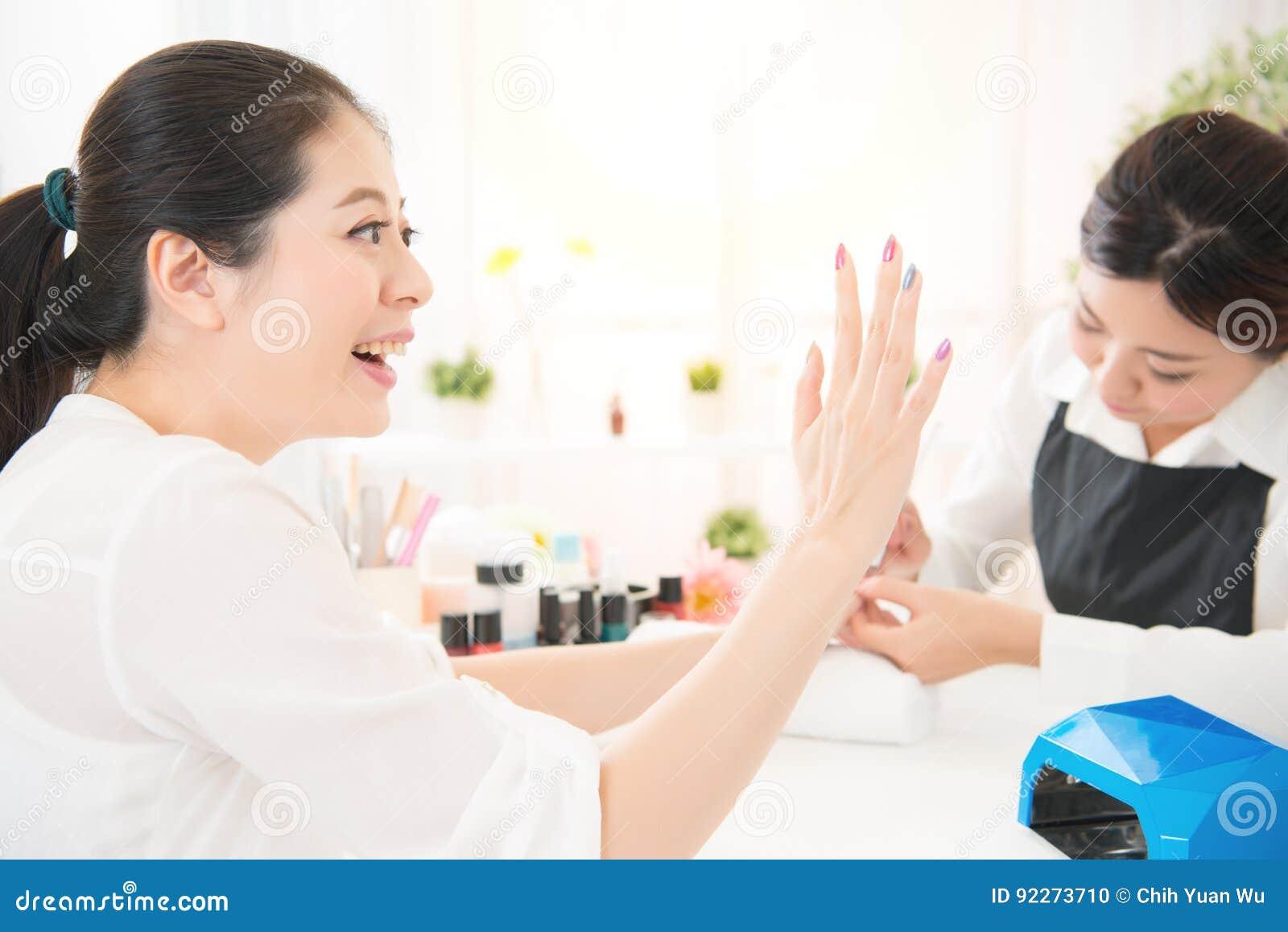 La femme enthousiaste aiment sa nouvelle manucure faite