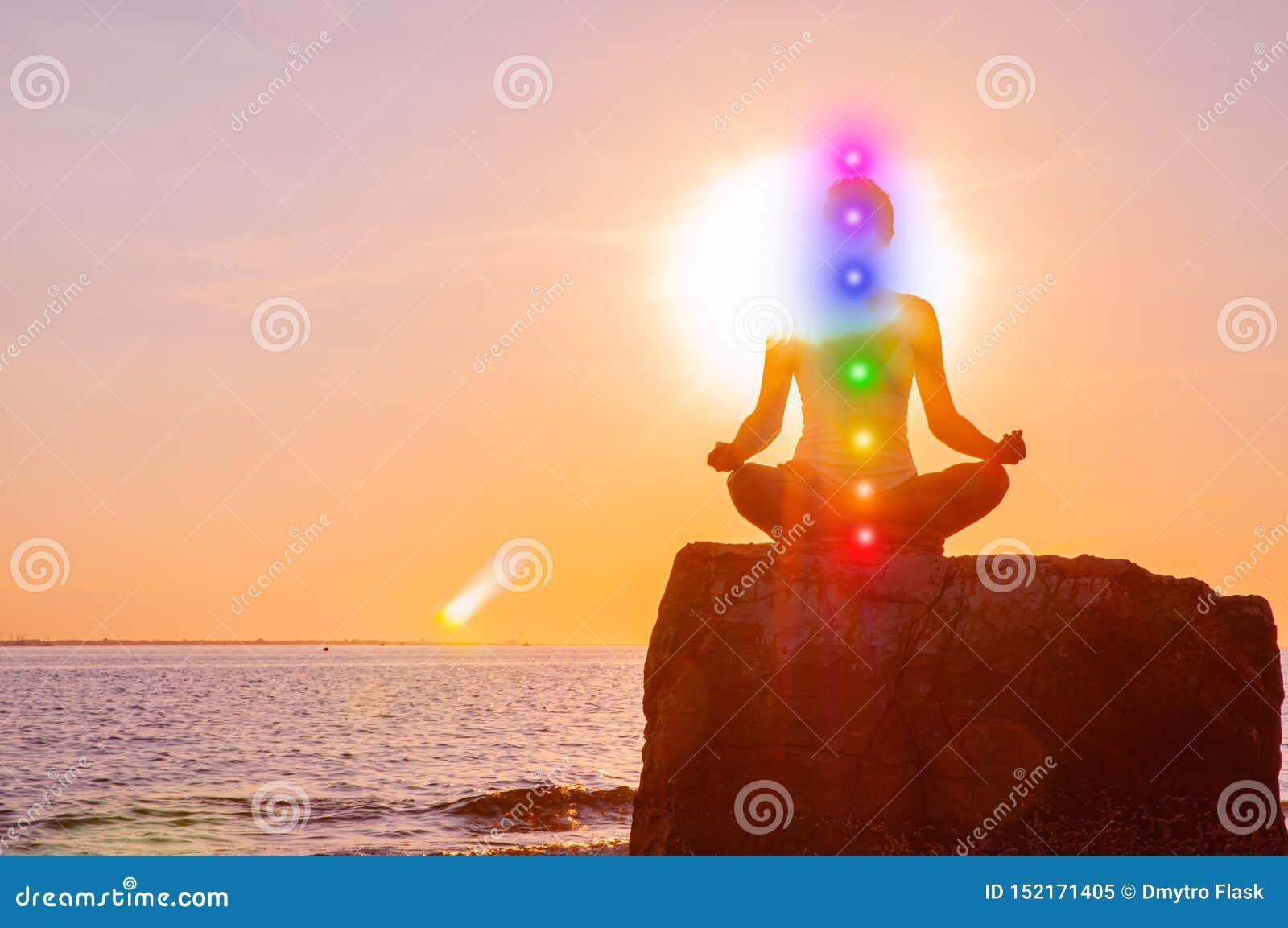 La femme est avec rougeoyer méditant sept chakras sur la pierre au coucher du soleil La silhouette de la femme pratique le yoga s