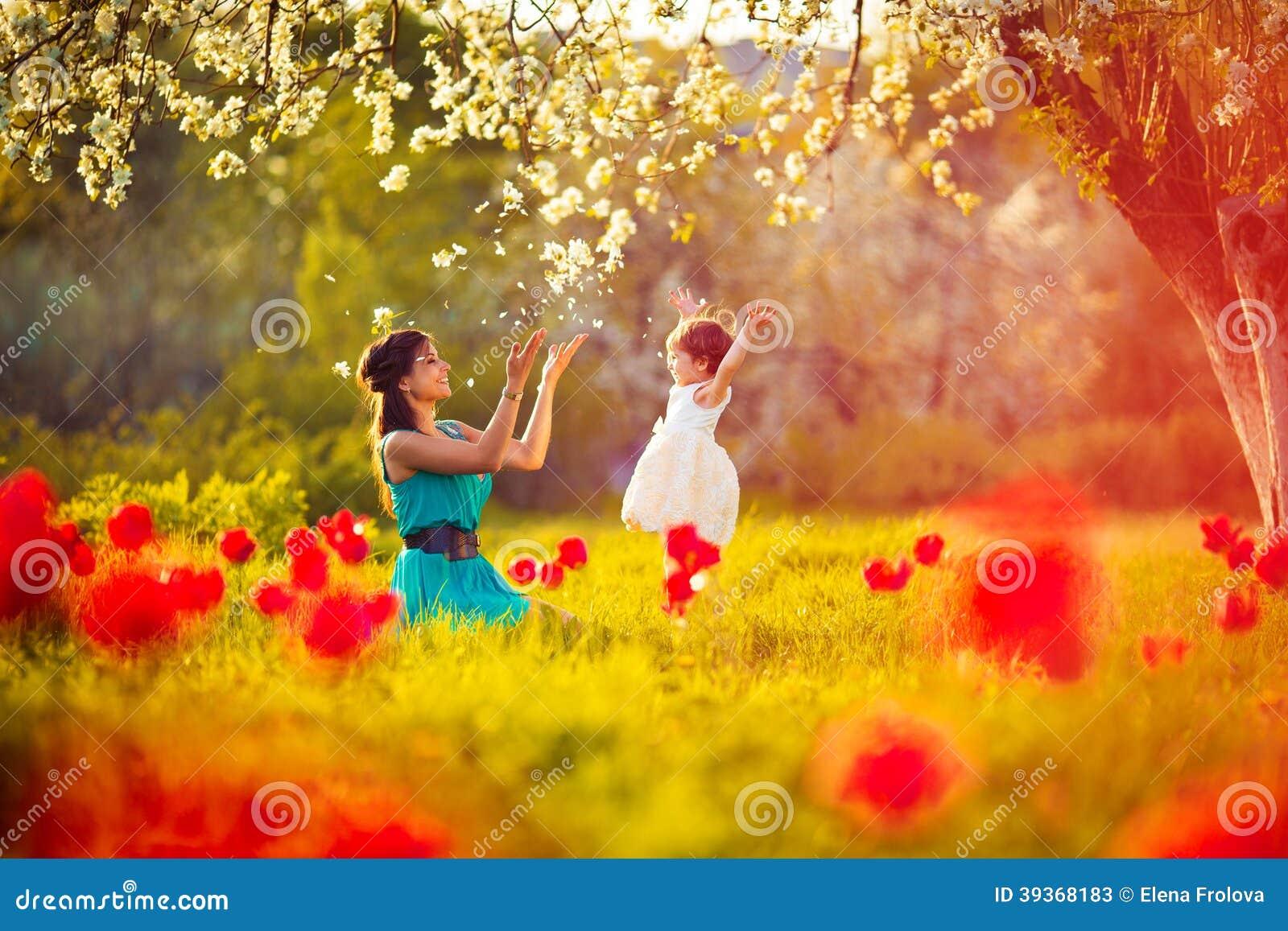 La femme et l enfant heureux pendant le ressort de floraison font du jardinage. Jour de mères