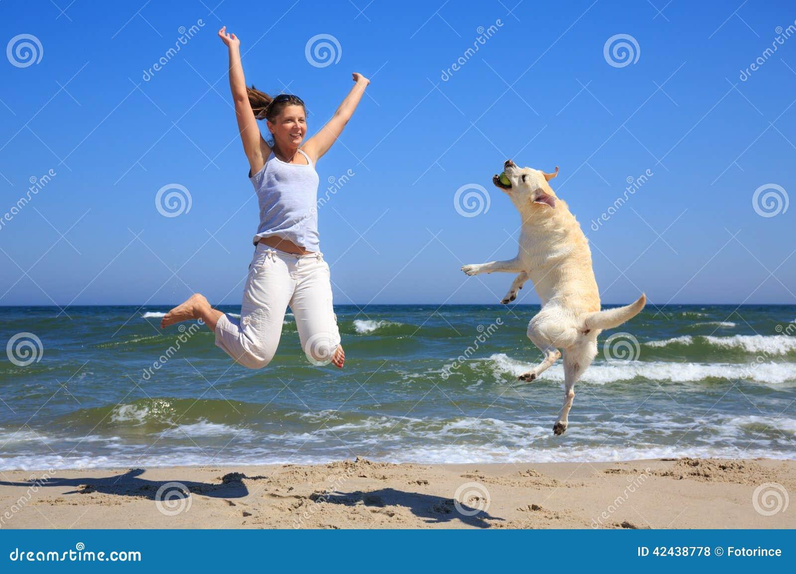 La femme et le chien multiplient Labrador sautant sur la plage