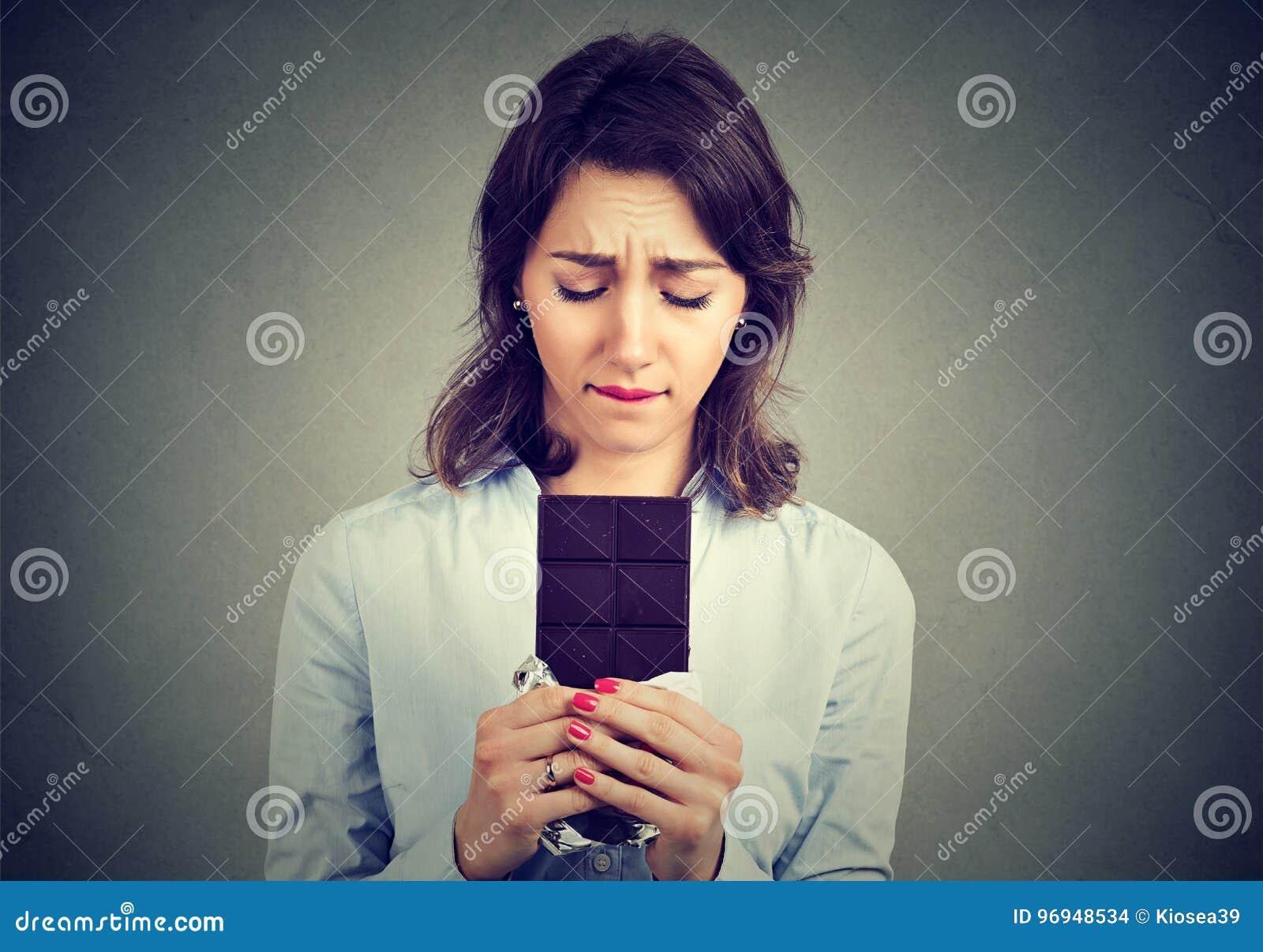 La femme a fatigué des restrictions de régime implorant la barre de chocolat