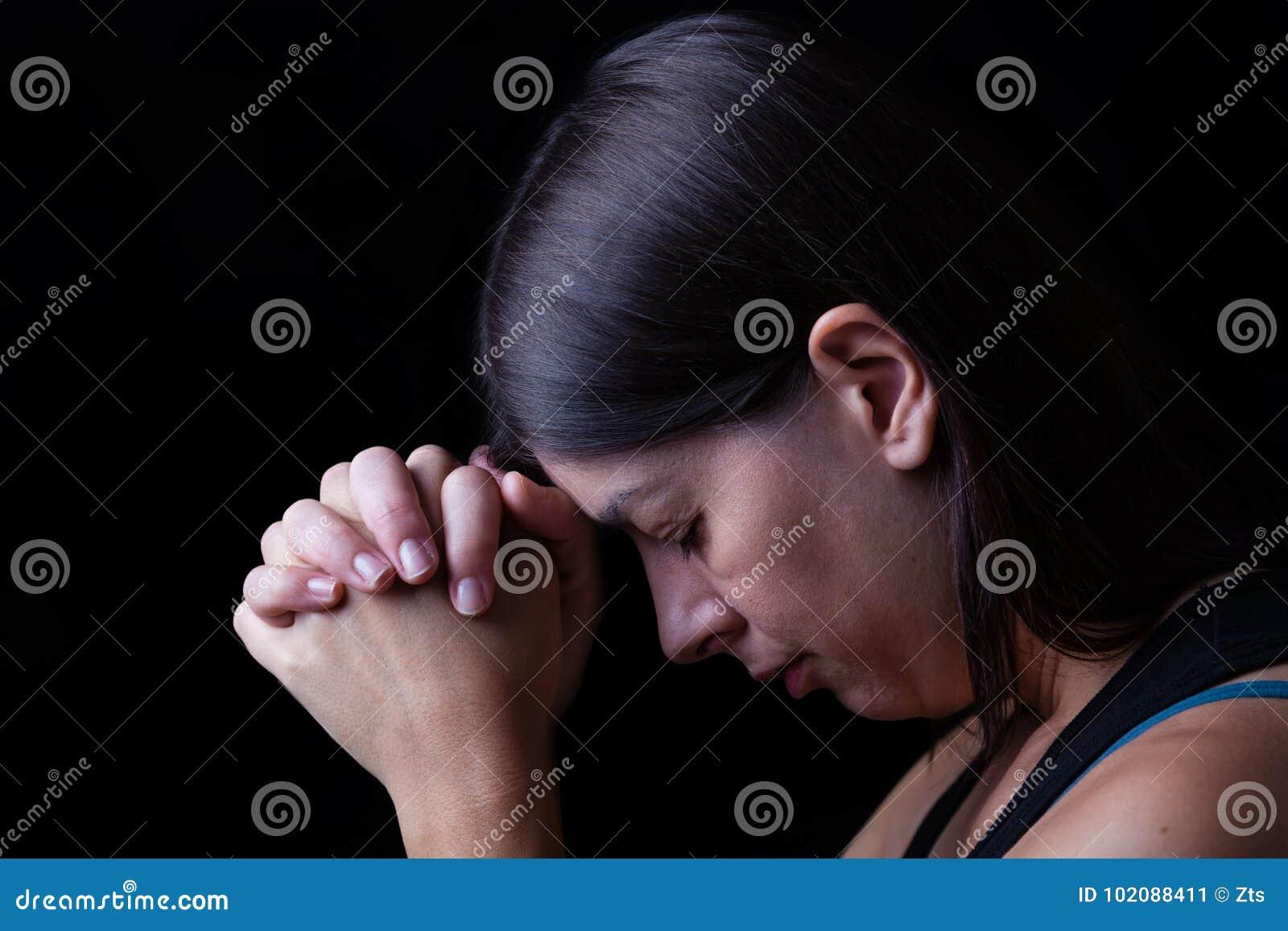 La femme fidèle priant, mains s est pliée dans le culte à un dieu
