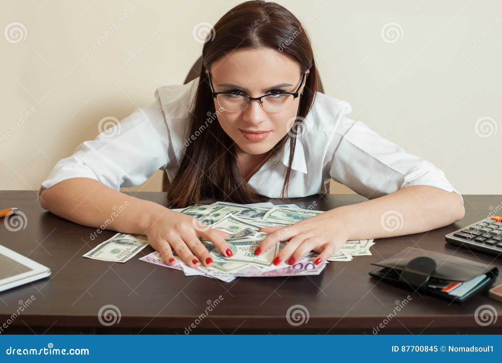 La femme heureuse d affaires étreint beaucoup d argent