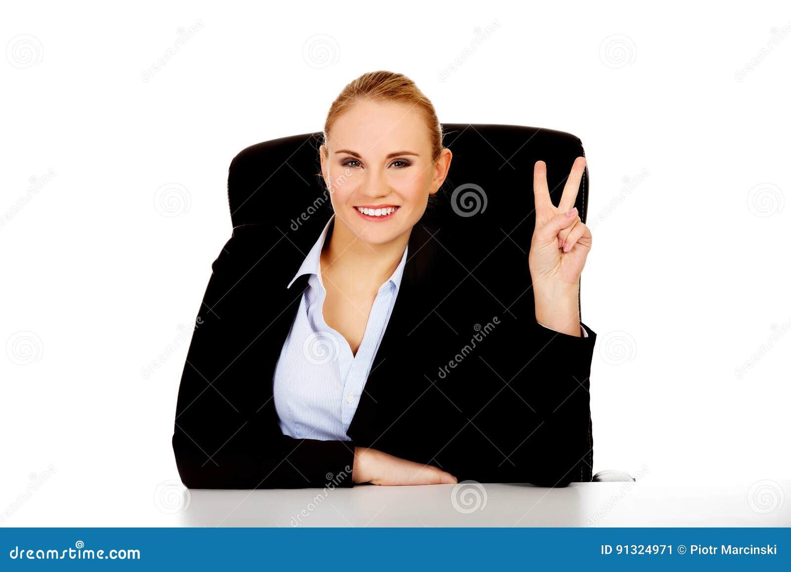 La femme heureuse d affaires s asseyant derrière le bureau et la victoire d expositions signent