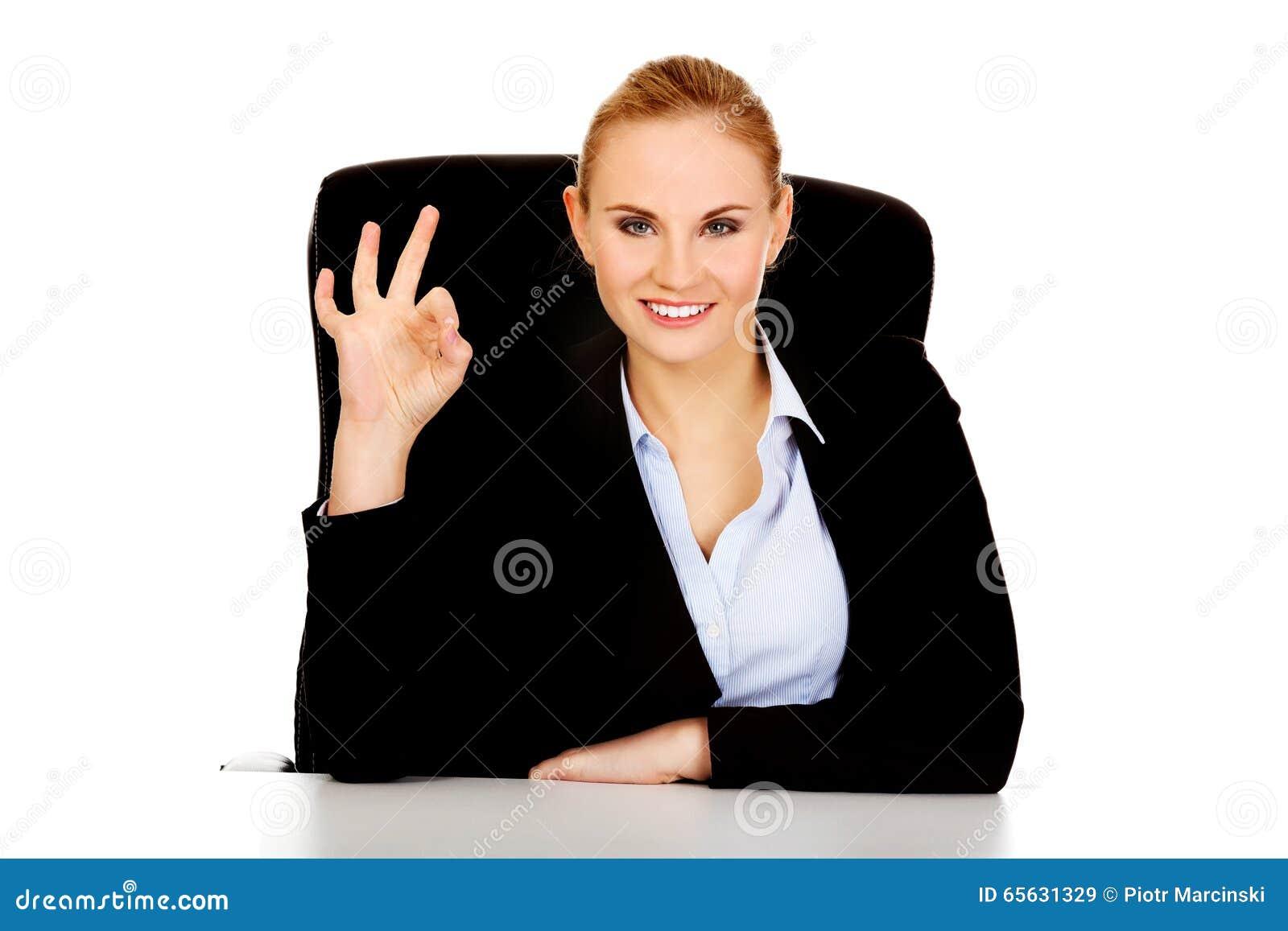 La femme heureuse d affaires s asseyant derrière le bureau et les expositions signent CORRECT