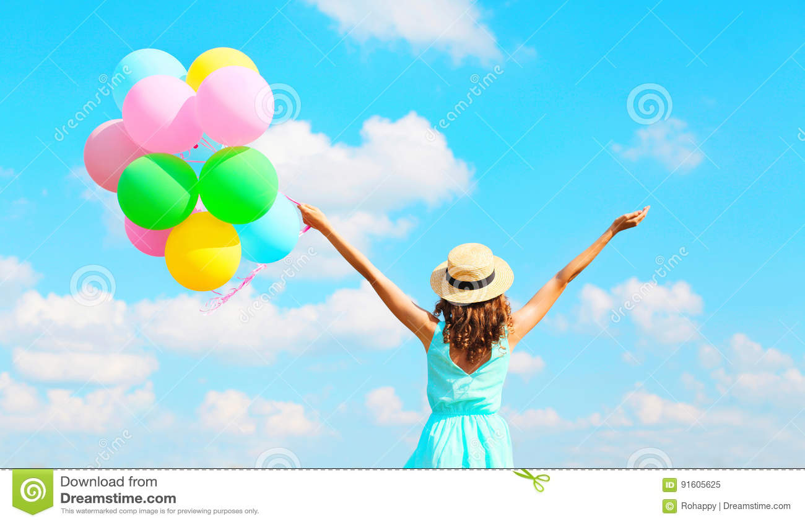 La femme heureuse de vue arrière avec les ballons colorés d un air apprécie un jour d été sur le fond de ciel bleu