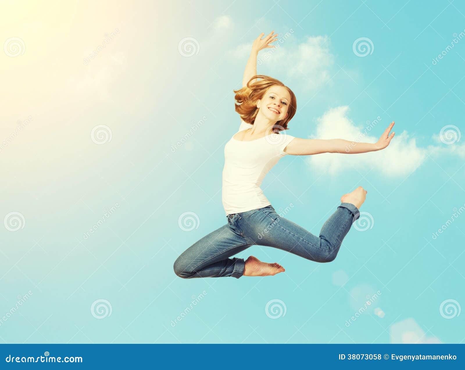 La femme heureuse sautent dans le ciel