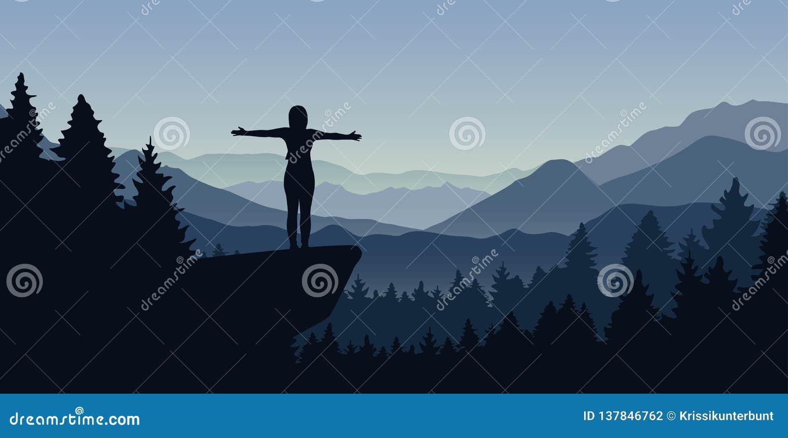 La femme heureuse se tient sur une falaise dans la forêt avec le paysage de nature de Mountain View