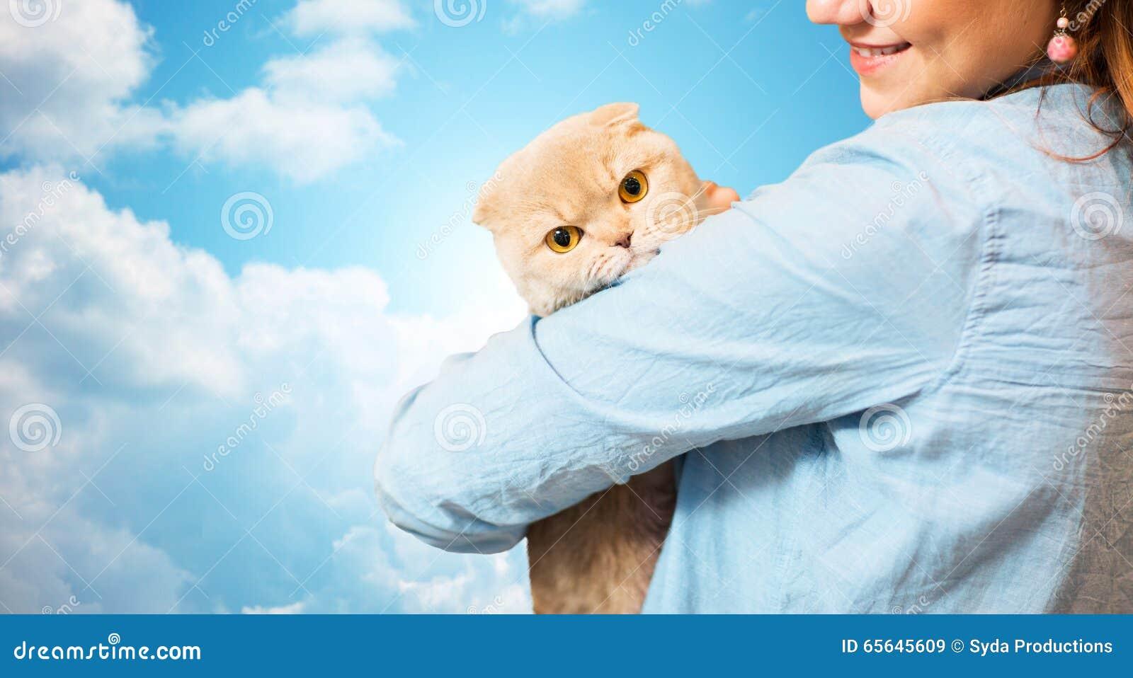La femme heureuse tenant l écossais plient le chat au-dessus du ciel