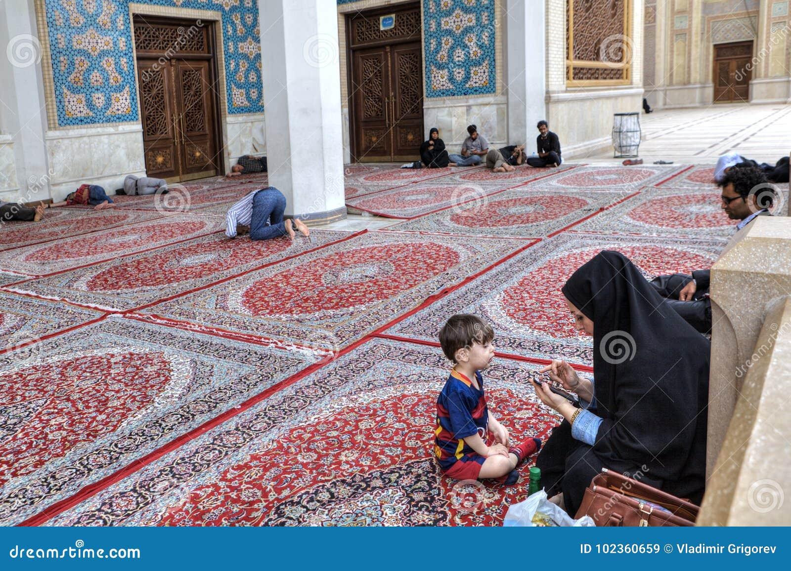 La femme islamique avec l enfant s assied dans la cour de la mosquée