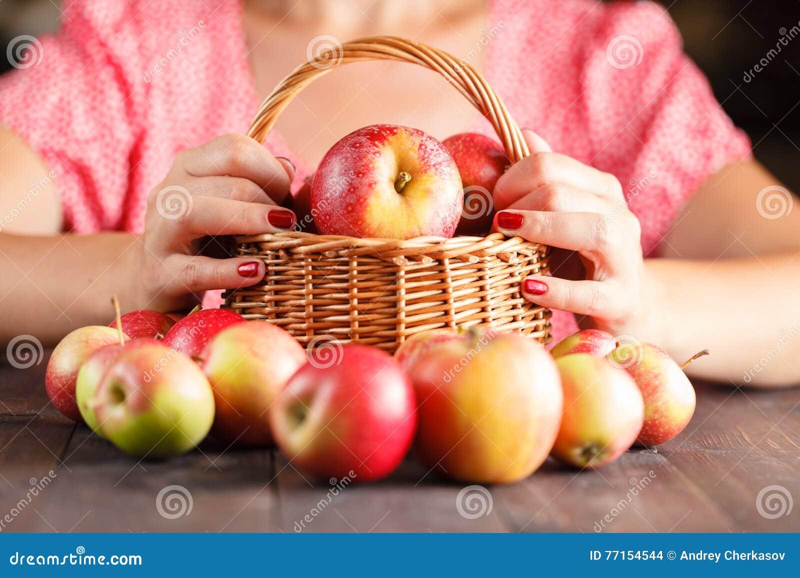 La femme juge un panier en osier plein des pommes rouges