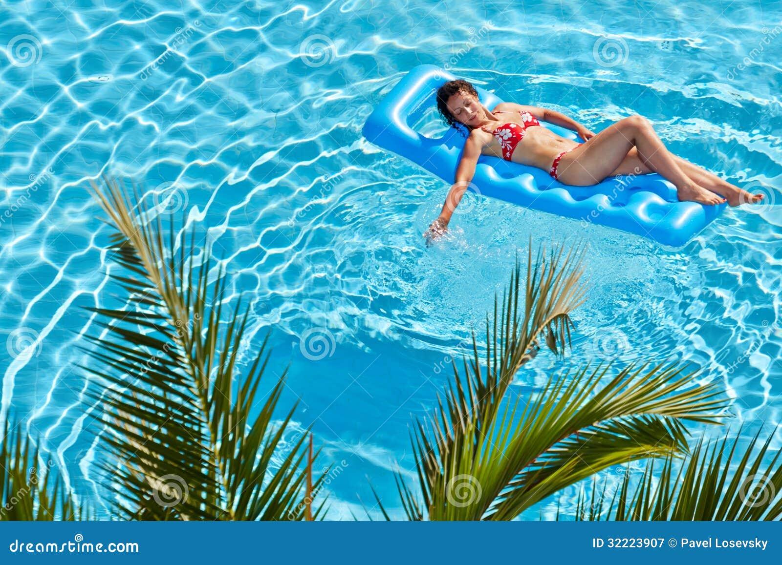 La femme la prend un bain de soleil sur le matelas - Bain de soleil piscine ...