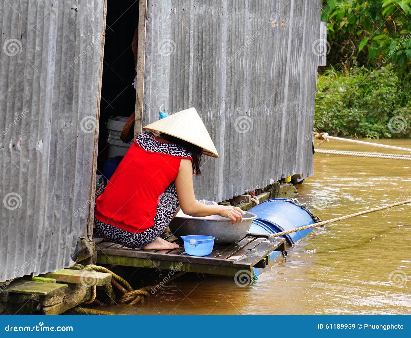 La femme locale prépare le repas sur son bateau