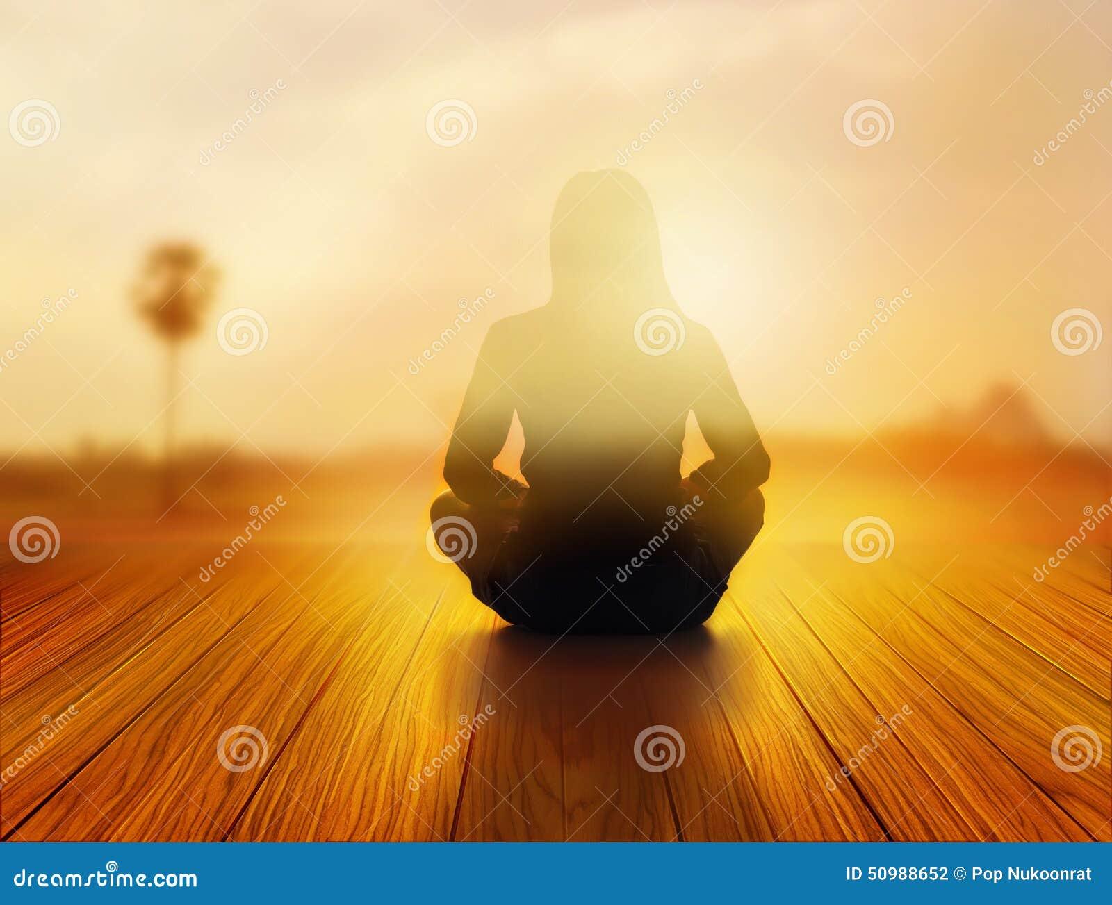 La femme méditait dans le lever de soleil et les rayons de la lumière sur le paysage, le concept vibrant doux et de tache floue