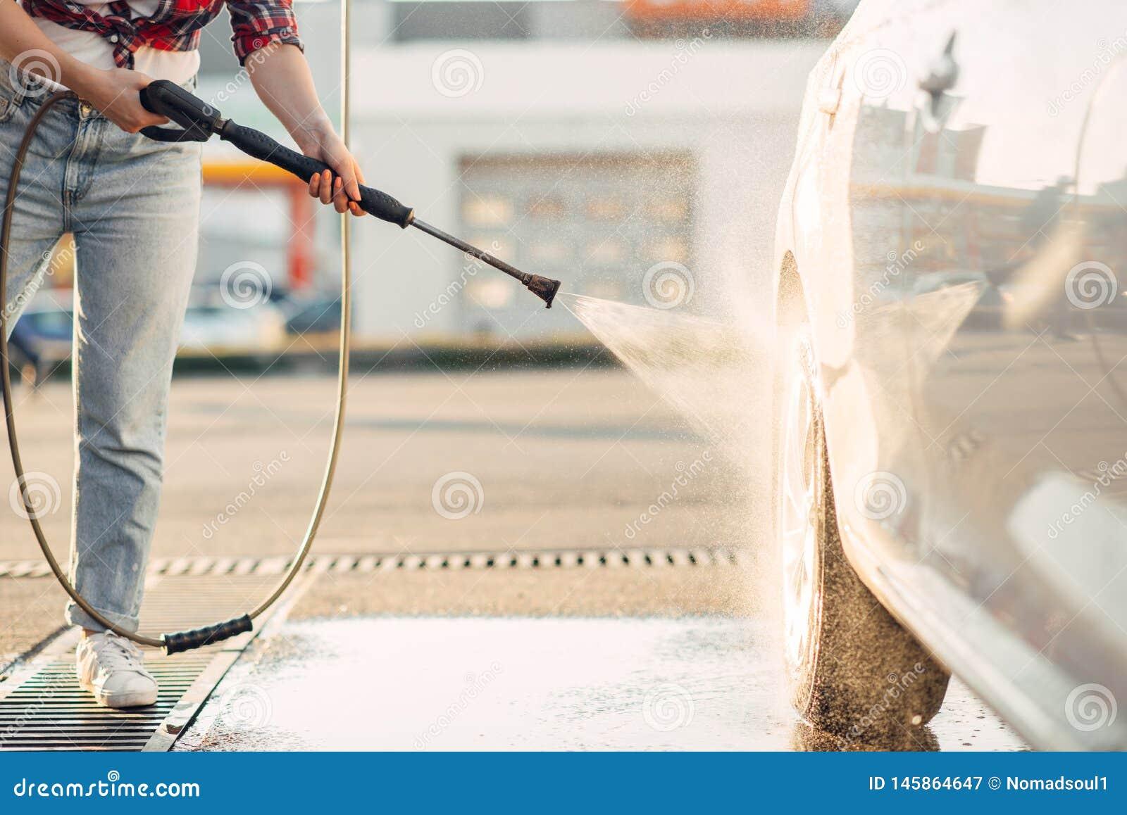 La femme mignonne nettoie des roues de voiture avec l arme ? feu d eau