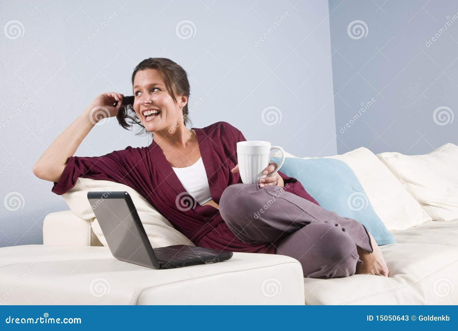 La femme moderne a détendu sur le divan avec le téléphone, ordinateur portatif