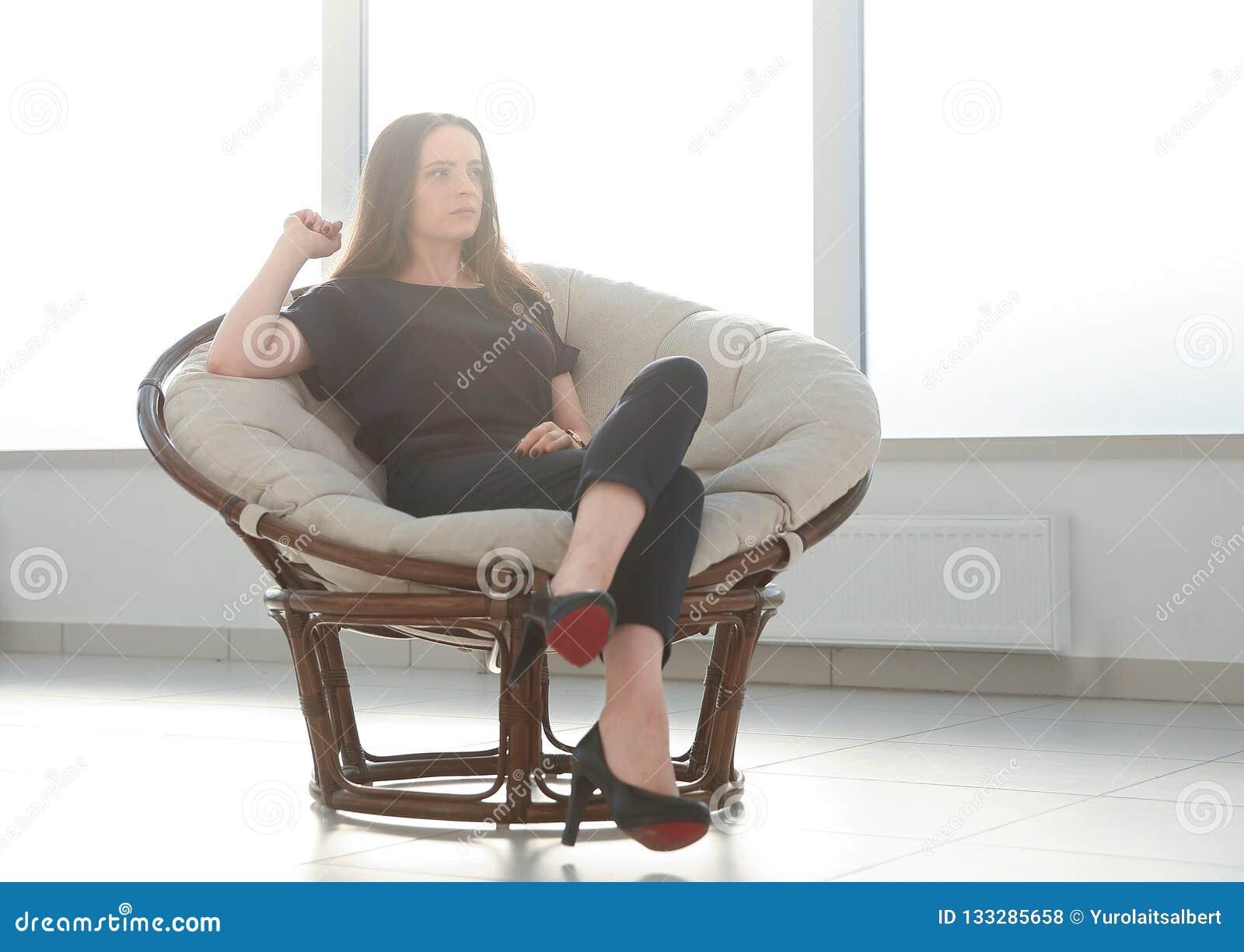 La femme moderne d affaires détend dans une chaise confortable