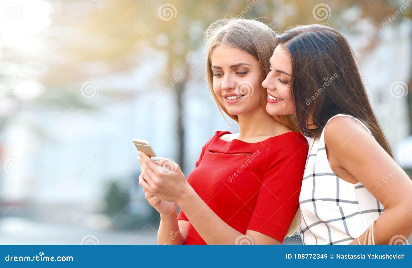 La femme montre à un téléphone portable quelque chose à son amie