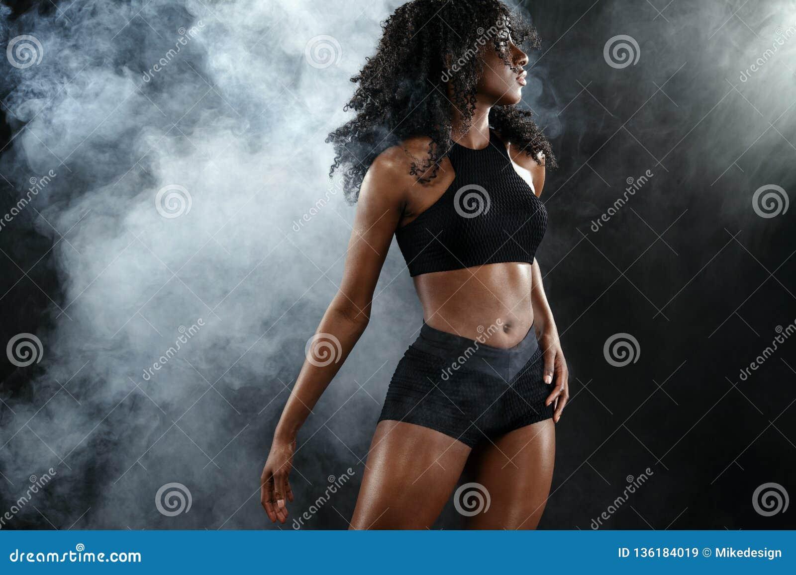La femme noire convenable sportive de peau, athlète fait la forme physique s exerçant sur le fond foncé
